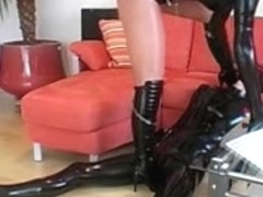 Blonde mistress in latex jerking a male slave
